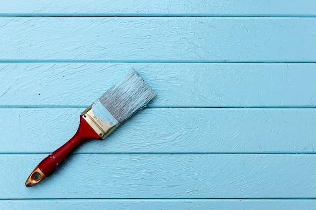 Vista dall'alto di pennelli di vernice rossa su colore pastello blu della tavola di legno. concetto di oggetto o carta da parati. Foto Premium