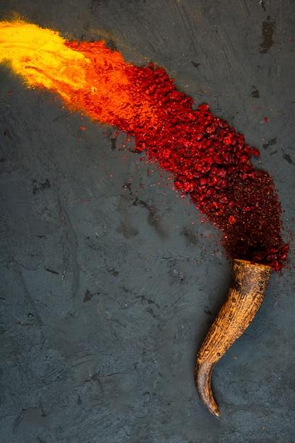 Vista dall'alto di peperoncino rosso e spezie in polvere di sommacco con curry sparsi da un corno sul nero Foto Gratuite
