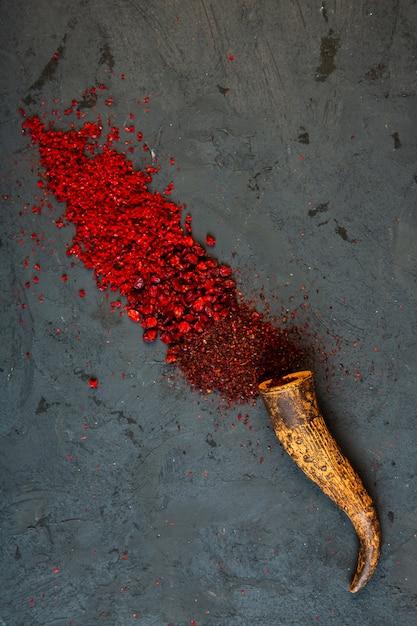 Vista dall'alto di peperoncino rosso e spezie in polvere di sumac sparse da un corno sul nero Foto Gratuite