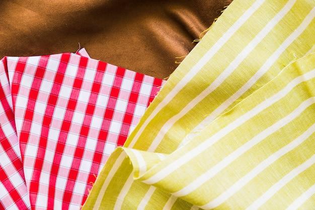 Vista dall'alto di percalle rosso con due tessuti Foto Gratuite