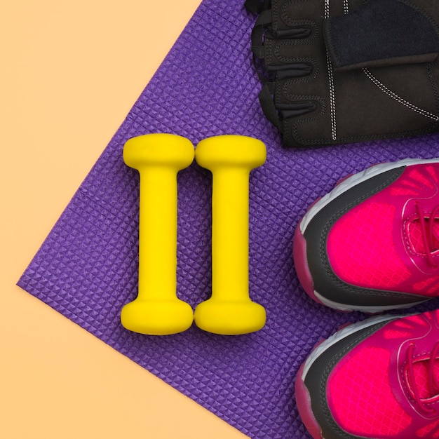 Vista dall'alto di pesi con guanti da ginnastica e scarpe da ginnastica Foto Gratuite