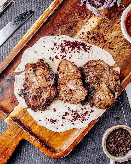 Vista dall'alto di pezzi di carne arrosto su una tavola di legno Foto Gratuite