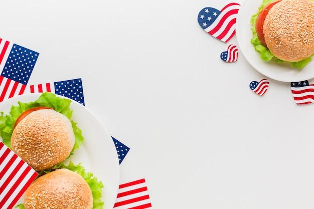 Vista dall'alto di piatti con bandiere americane e hamburger Foto Gratuite