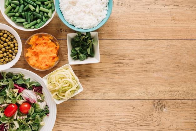 Vista dall'alto di piatti con insalata e riso Foto Gratuite