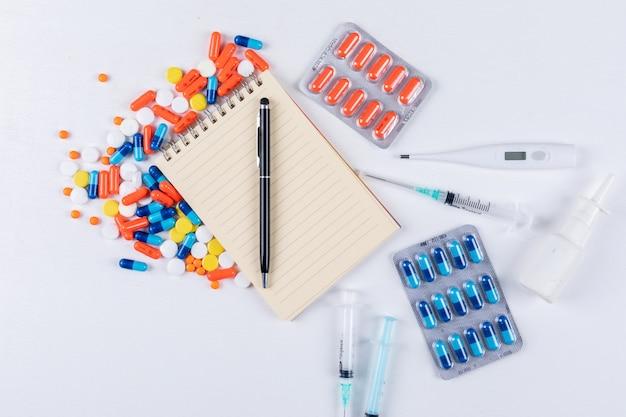 Vista dall'alto di pillole colorate con blocco note, penna, termometro, spray nasale e ago Foto Gratuite