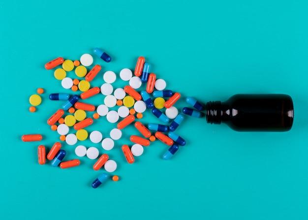 Vista dall'alto di pillole colorate dalla bottiglia Foto Gratuite