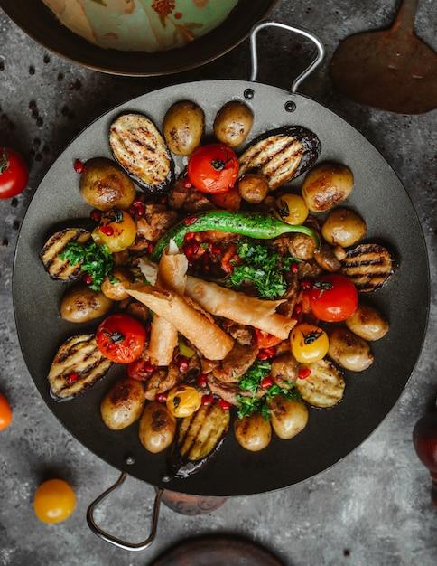 Vista dall'alto di pollo saj con pepe, melanzane, pomodori, patate e focaccia Foto Gratuite
