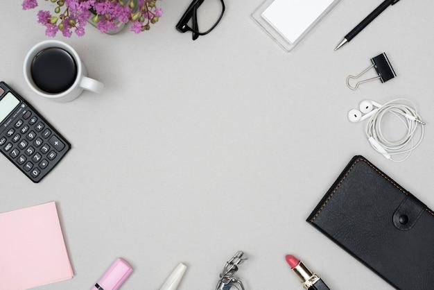 Vista dall'alto di prodotti cosmetici; cancelleria per ufficio; tazza di caffè; occhiali disposti su sfondo grigio Foto Gratuite