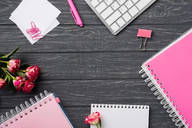 Vista dall'alto di quaderni sulla scrivania in legno con bouquet di rose e graffette Foto Gratuite