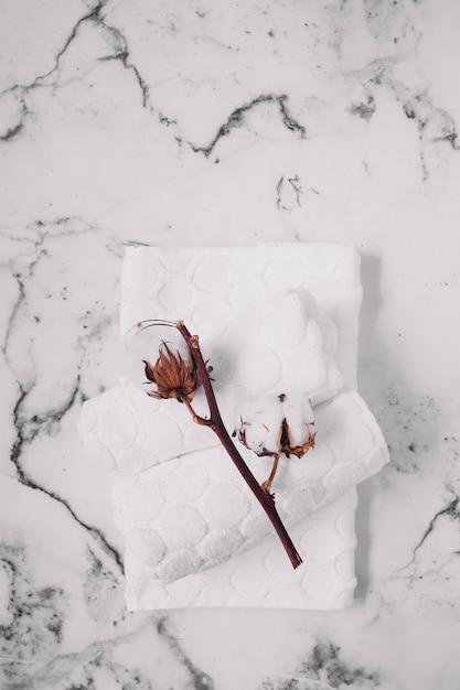 Vista dall'alto di ramoscello di cotone e tovaglioli bianchi su sfondo di marmo Foto Gratuite