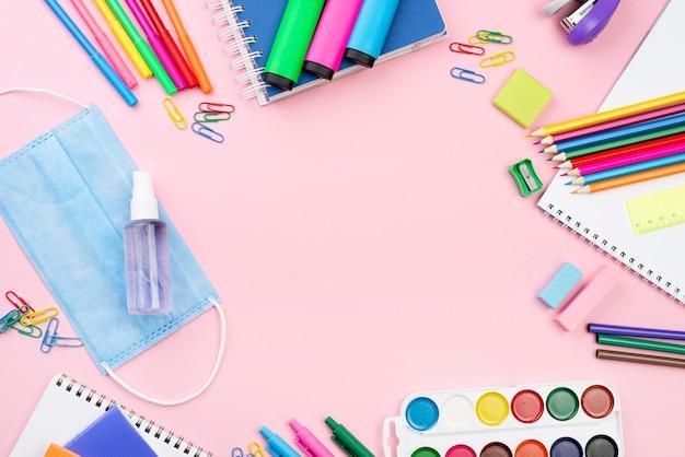 Vista dall'alto di ritorno a scuola essenziale con matite e mascherina medica Foto Gratuite