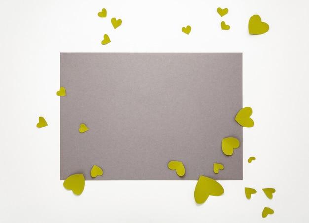 Vista dall'alto di san valentino decorazioni piatte laici. cuori gialli verdi su fondo grigio. felice san valentino banner Foto Premium