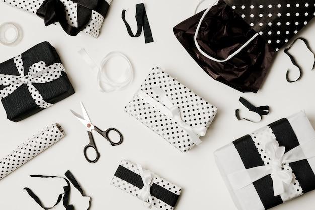 Vista dall'alto di scatole regalo con carta design; forbice e sacchetto di carta Foto Gratuite