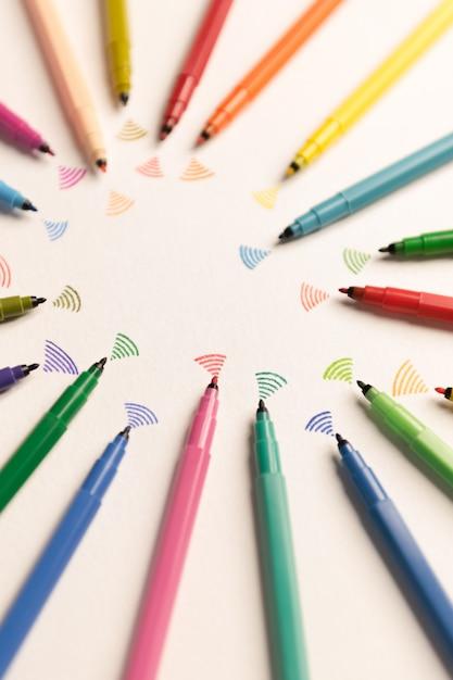 Vista dall'alto di scioperi dipinti con pennarelli colorati su carta bianca. marekrs inviando wi-fi Foto Gratuite