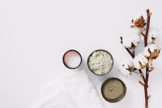 Vista dall'alto di scrub; candela; tovagliolo e ramoscello di cotone su superficie bianca Foto Gratuite