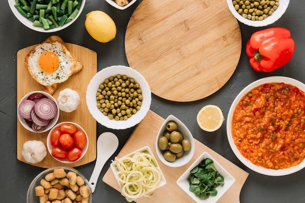 Vista dall'alto di taglieri con uovo fritto e olive Foto Gratuite