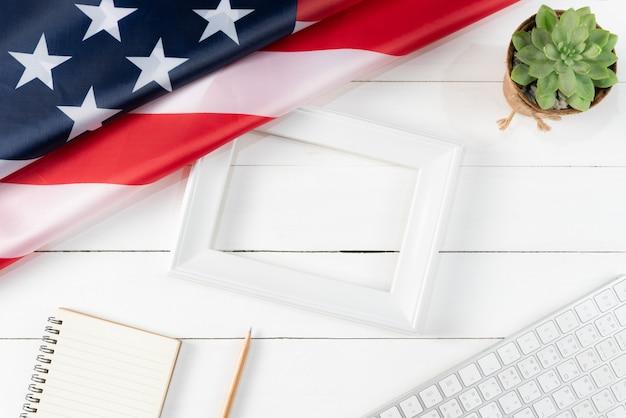 Vista dall'alto di tastiera, libro, matita, cornice bianca e bandiera americana su fondo di legno bianco Foto Premium