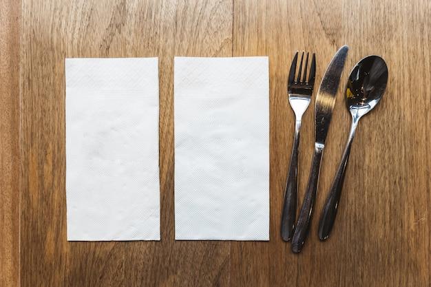 Vista dall'alto di tovaglioli di tessuto e posate sul tavolo di legno. per banner di cibo. Foto Premium