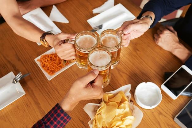 Vista dall'alto di tre amici irriconoscibili brindando con boccali di birra Foto Gratuite