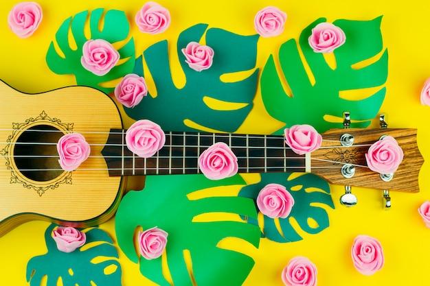 Vista dall'alto di un modello di fiori rosa e chitarra su sfondo giallo vibrante Foto Premium