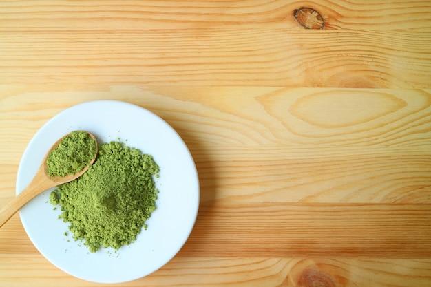 Vista dall'alto di un piatto di polvere di tè verde matcha con un cucchiaio da tè in legno sul tavolo di legno Foto Premium