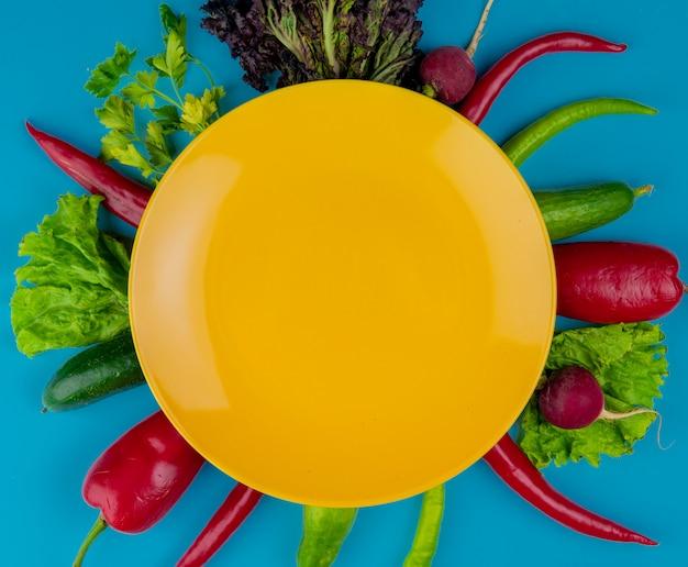 Vista dall'alto di un piatto giallo vuoto su verdure fresche cetrioli ravanello rosso e verde peperoncino e lattuga su sfondo blu Foto Gratuite