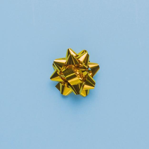 Vista dall'alto di un singolo arco regalo sulla semplice superficie blu Foto Gratuite