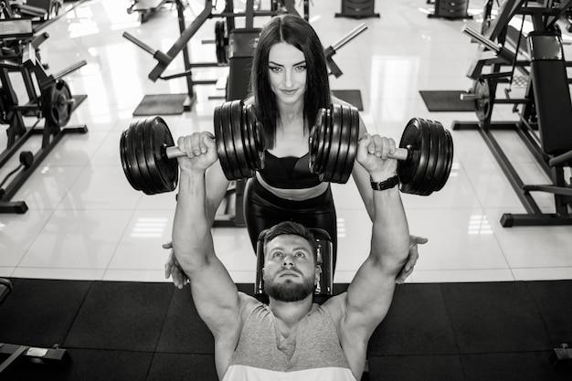Vista dall'alto di una bella donna in abiti sportivi aiutare l'uomo forte a sollevare manubri. foto in bianco e nero di bella coppia nella palestra di sport che si esercita con le teste di legno. Foto Premium