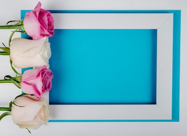 Vista dall'alto di una cornice vuota con rose bianche e rosa su sfondo blu con spazio di copia Foto Gratuite