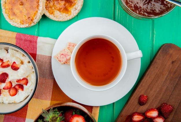 Vista dall'alto di una tazza di tè con cioccolato bianco sulla bustina di tè e ciotola di ricotta con fette biscottate e marmellata di pesche sulla superficie verde Foto Gratuite