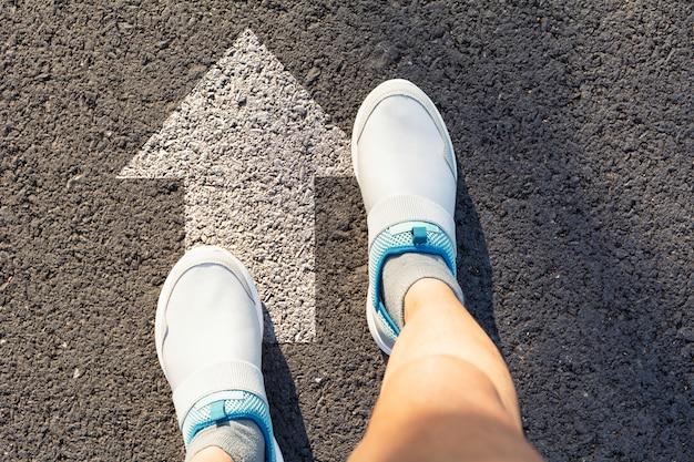 Vista dall'alto di uomo che indossa scarpe bianche scegliendo un modo segnato con frecce bianche Foto Premium