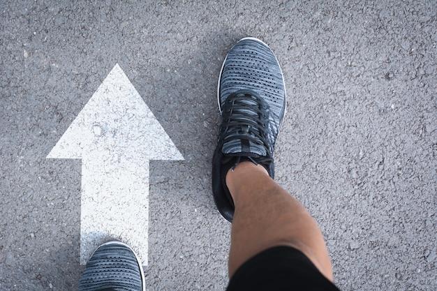 Vista dall'alto di uomo che indossa scarpe scegliendo un modo segnato con frecce bianche. Foto Premium