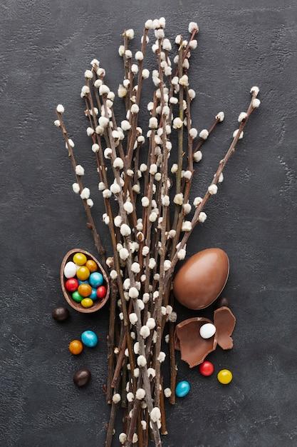 Vista dall'alto di uova di pasqua al cioccolato con caramelle colorate all'interno e fiori Foto Gratuite
