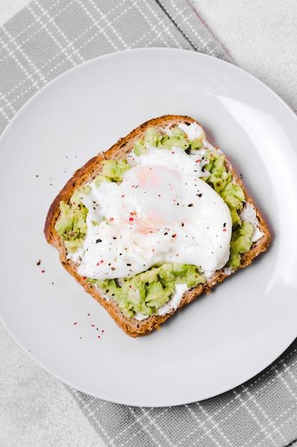 Vista dall'alto di uovo con avocado toast sul piatto Foto Gratuite