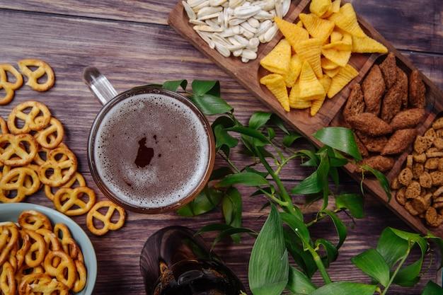 Vista dall'alto di vari snackersunflower di birra patatine cracker e mini salatini con un boccale di birra su rustico Foto Gratuite