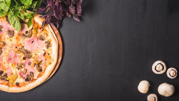 Vista dall'alto di verdure a foglia; funghi e pizza su sfondo scuro Foto Gratuite