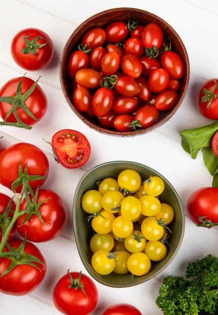 Vista dall'alto di verdure come spinaci di pomodoro coriandolo con ciotole di pomodori su legno Foto Gratuite