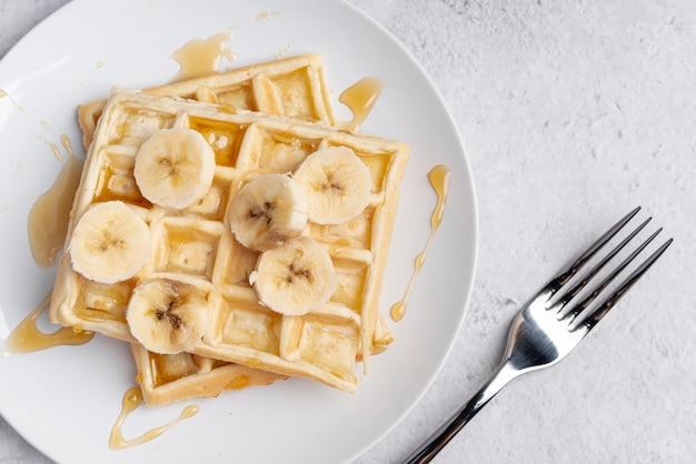 Vista dall'alto di waffle con fettine di banana e miele Foto Gratuite