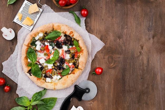 Vista dall'alto disposizione della pizza e della taglierina Foto Gratuite