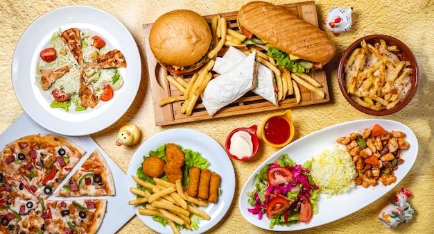 Vista dall'alto fast food mix hamburger doner sandwich crocchette di pollo insalata di verdure di riso bastoncini di pollo insalata di caesar funghi pizza pollo ragù patatine fritte maionese un Foto Gratuite