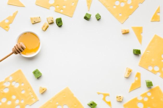 Vista dall'alto fette di formaggio emmental con cornice di miele Foto Gratuite