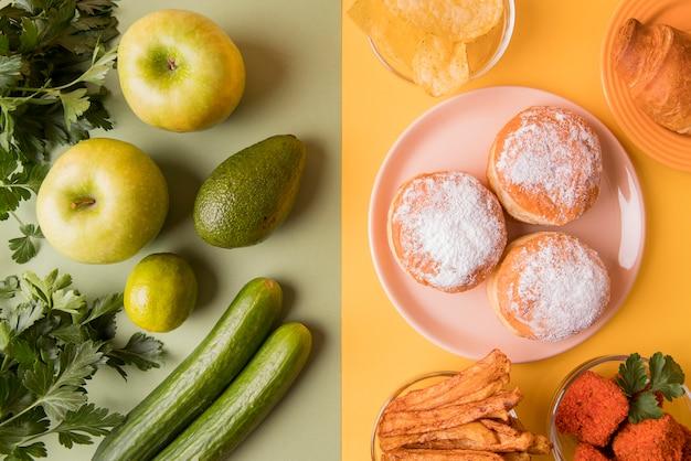 Vista dall'alto frutta e verdura con spuntini malsani Foto Gratuite