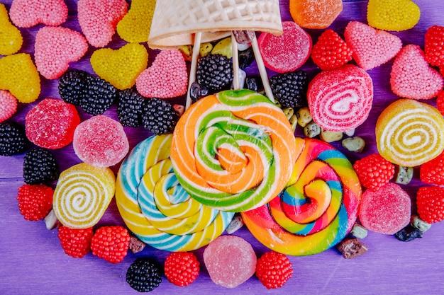 Vista dall'alto ghiaccioli colorati con marmellata colorata di varie forme e corna di cialda su uno sfondo viola Foto Gratuite