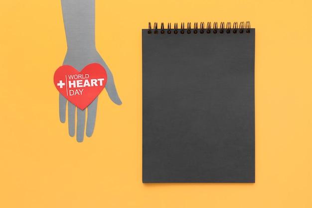 Vista dall'alto giornata mondiale del cuore con blocco note Foto Gratuite
