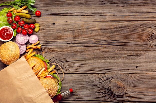 Vista dall'alto hamburger con patatine fritte in una borsa Foto Gratuite