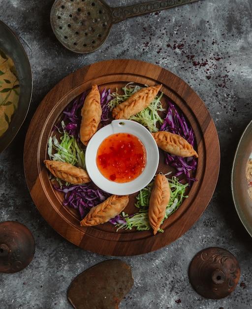 Vista dall'alto khinkali arrostito e servito con erbe e salsa di peperoncino. Foto Gratuite