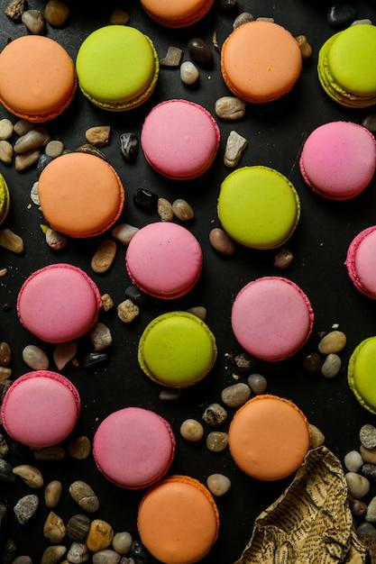 Vista dall'alto macarons multicolore con ciottoli sul tavolo nero Foto Gratuite