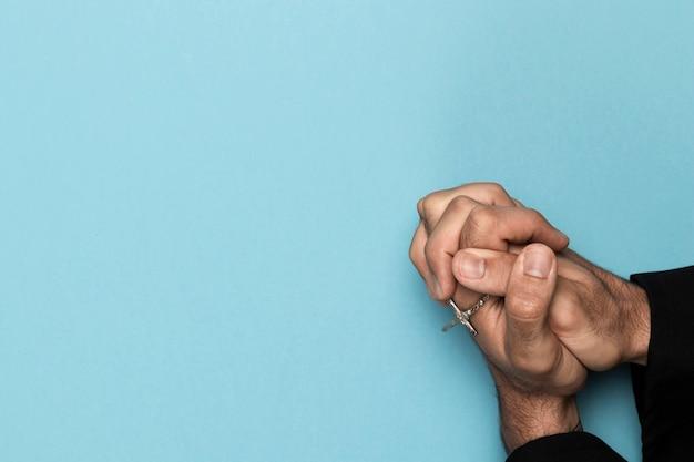 Vista dall'alto mani che tengono la collana santa Foto Gratuite