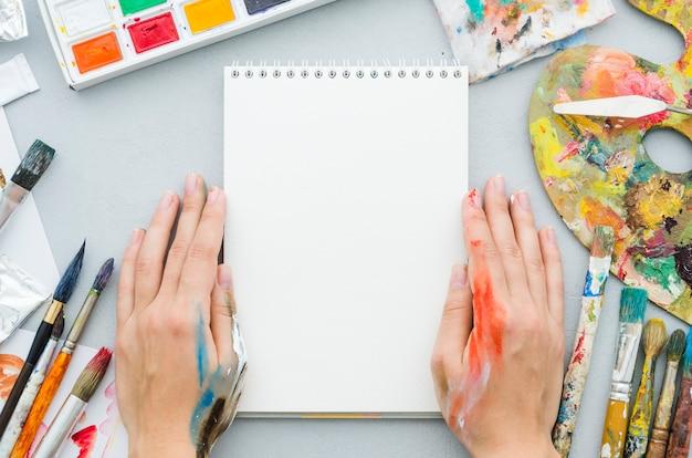 Vista dall'alto mani con notebook circondato da elementi di pittura Foto Gratuite