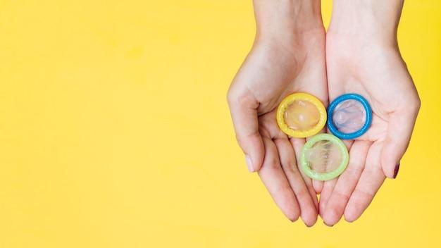 Vista dall'alto mani in possesso di preservativi con copia-spazio Foto Gratuite